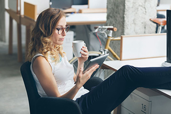 A woman sitting back reading a tablet while drinking coffee.