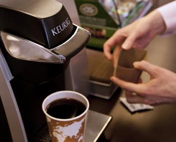 A person making a cup of coffee using a Keurig single cup brewer.