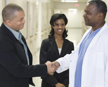 A doctor shaking hands with a procurement specialist.