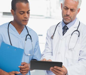 Two medical professionals reviewing documents on a tablet.