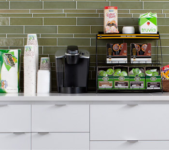 A breakroom counter with assorted coffee products.