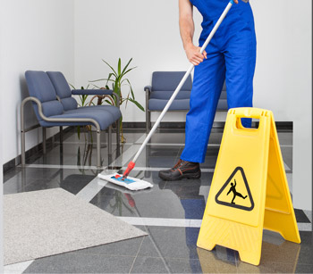 Person mopping the floor with a caution floor sign nearby.